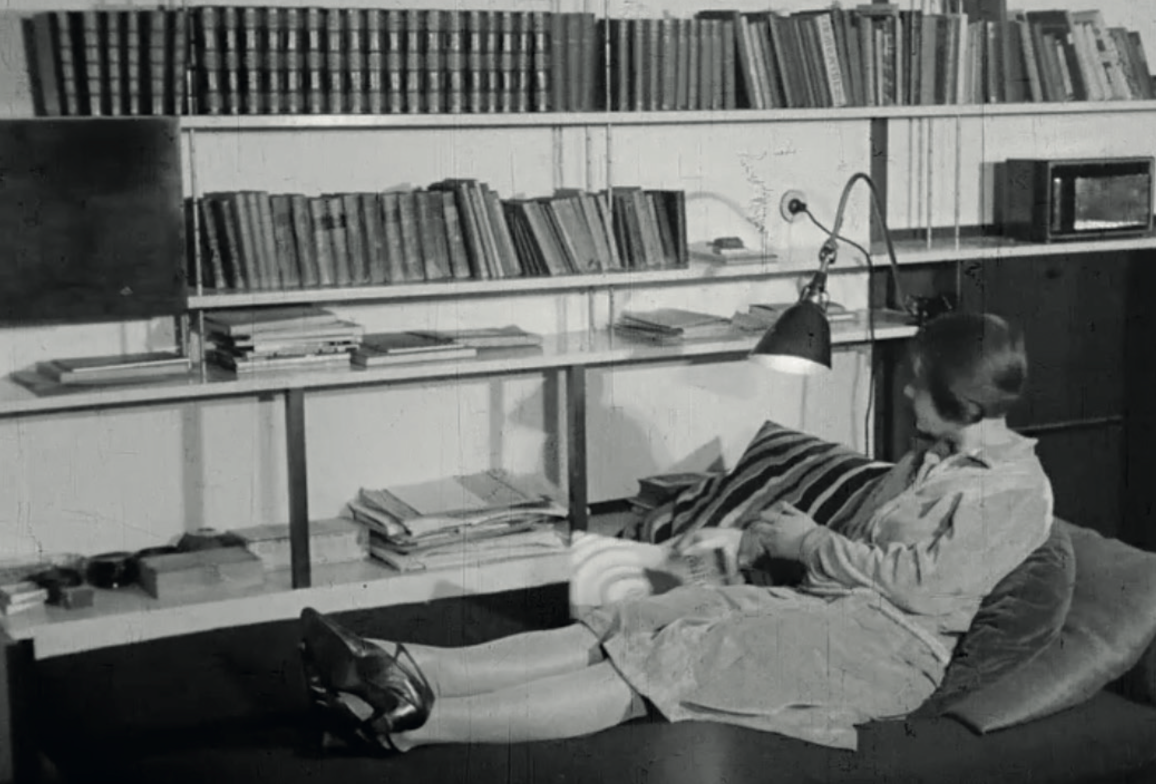 The large living room contains a desk and a library as well. The resting couch transforms into the seating for the tea corner. Image from: How to live healthily and economically? Film series in four episodes by Walter Gropius and the Humboldt film GMBH, 1926.