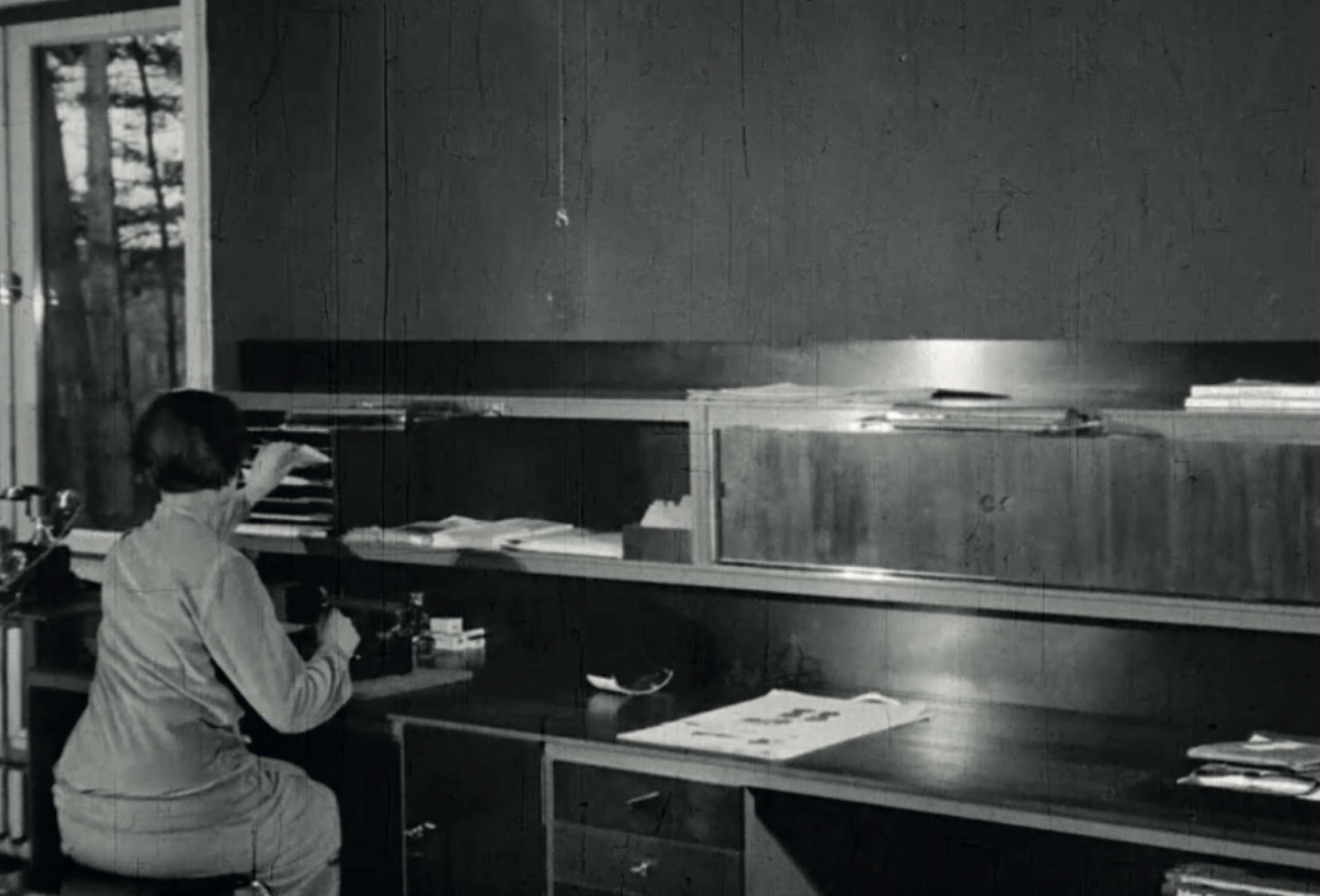 The big double desk. The desk also has a special lamp. Image from: How to live healthily and economically? Film series in four episodes by Walter Gropius and the Humboldt film GMBH, 1926.