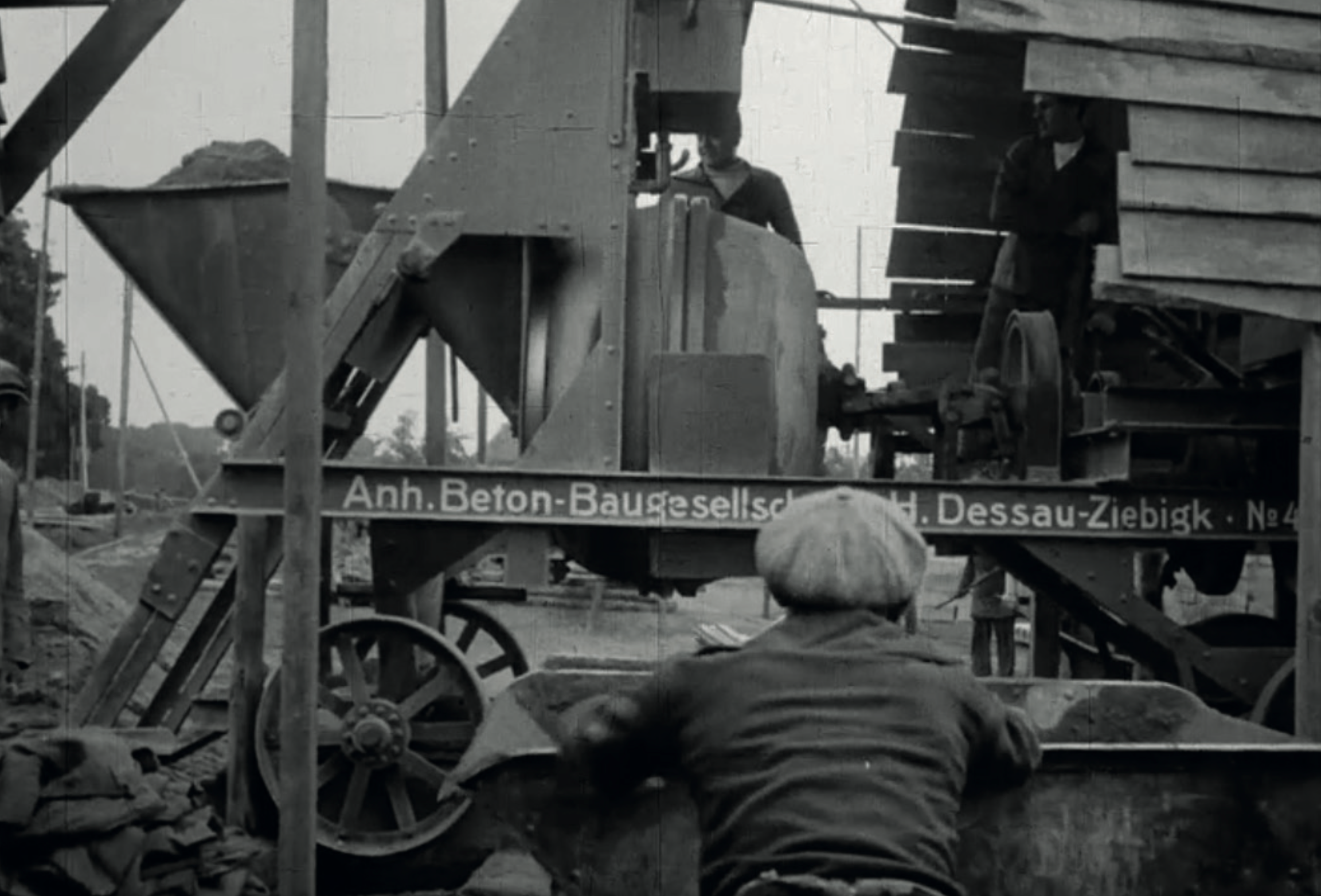 The concrete is mixed. The slab beams are reinforced concrete beams. The reinforcement process is achieved with a small apparatus. Image from: How to live healthily and economically? Film series in four episodes by Walter Gropius and the Humboldt film GMBH, 1926.